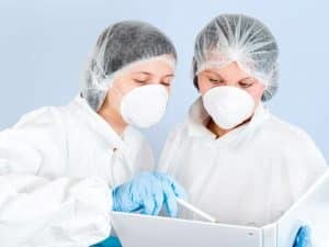 Female Pharmaceutical Clinical Researchers Check Compliance Records 300x225